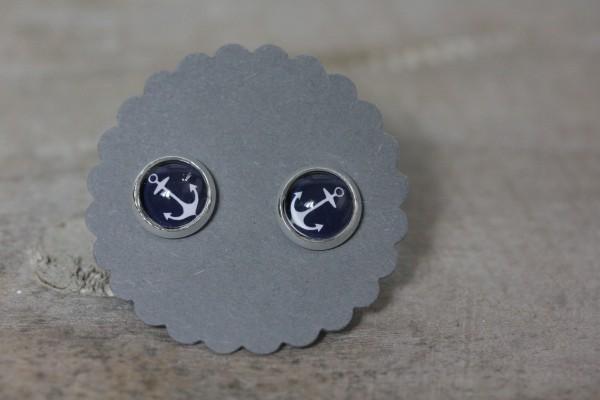 Kleine Ohrstecker blauer Hintergrund weißer Anker